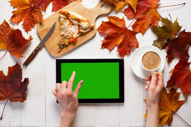 現代の若い女性の秋の朝。タブレット、コーヒー、アートをテーブルに。上面図。