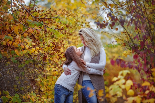 Autumn, mother and daughter in autumn park