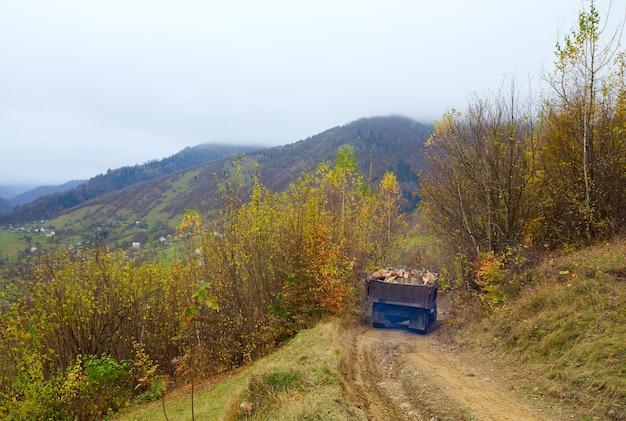 秋の山の汚れた道と古い丸太トラック
