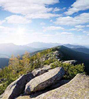 Осенний горный пейзаж с видом на каменный хребет в солнечный день с красивыми облаками