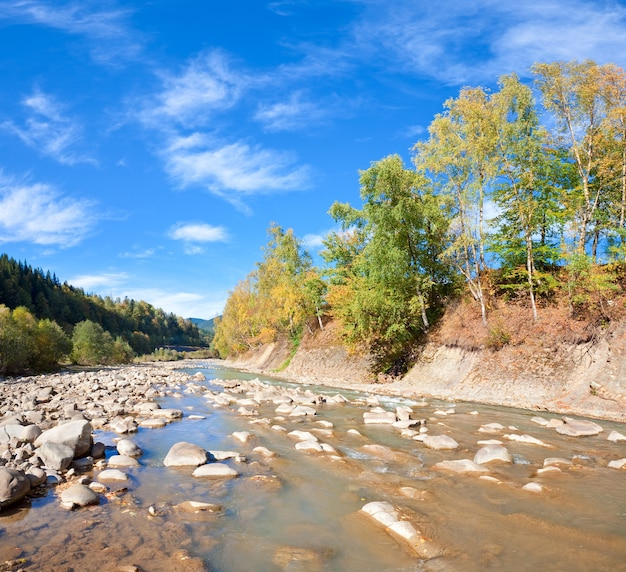 Autumn mountain stony river view with varicolored trees on riverside. two shots stitch image.