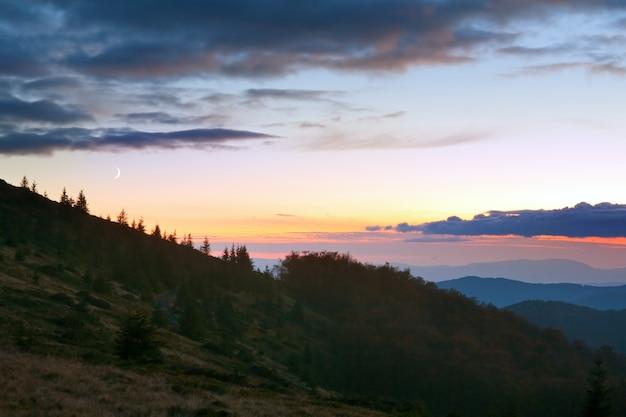Осенний горный закат и луна в вечернем зареве неба