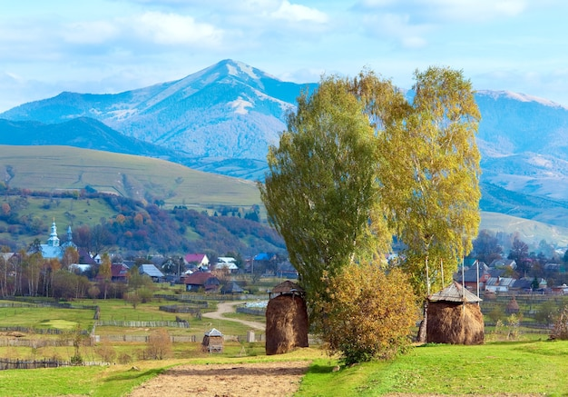 干し草の山と田舎の汚れた道がある秋の山間の村の郊外(kolochava、carpathian mt's、ウクライナ)。