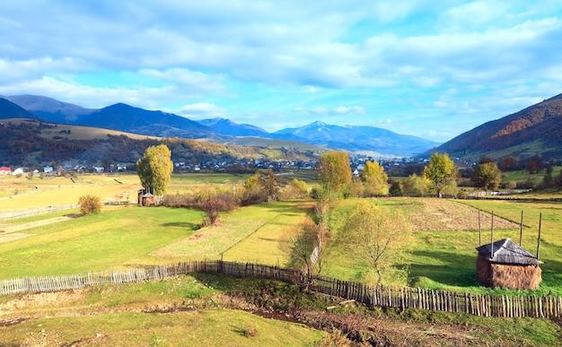 Осенняя окраина горной деревни со стогом сена и проселочной грязной дорогой (колочава, карпаты, украина).