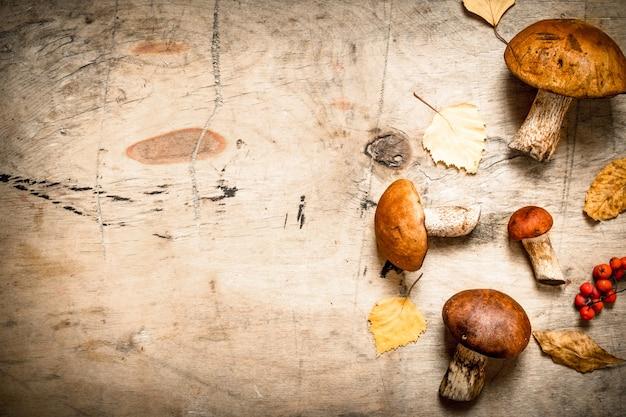 Осенние грибы с кленовыми листьями. на деревянном столе.
