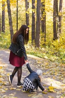 Концепция осени, природы и семьи - мать и ее ребенок гуляют в парке.