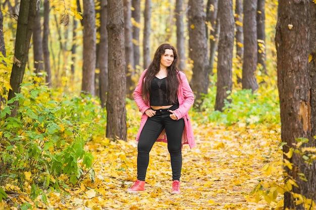 秋、自然と人々の概念-公園でピンクのジャケットのプラスサイズの女性の肖像画