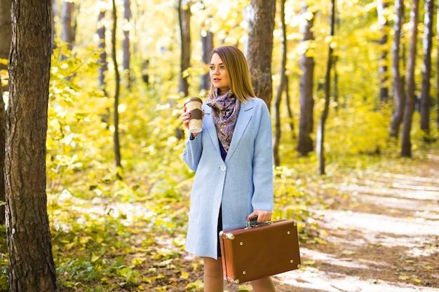 가을, 자연과 사람들 개념-커피 한 잔을 들고 블루 코트에 젊은 아름 다운 여자
