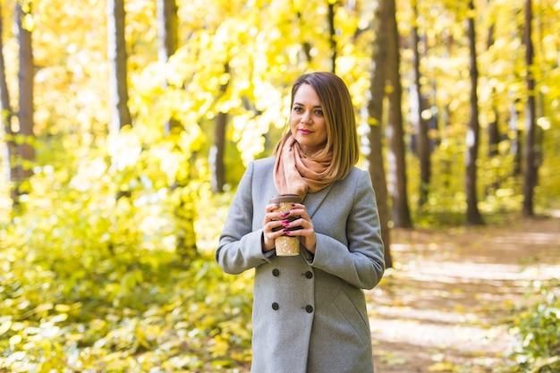 秋、自然と人々の概念-一杯のコーヒーを保持している灰色のコートを着た若い美しい女性