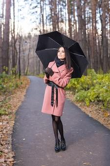 가을, 자연과 사람들이 개념-가을 비오는 공원에서 하늘을보고 젊은 여자.