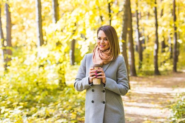 秋、自然、人々の概念-コーヒーを飲みながら公園の木に立っている青いコートを着た若い女性。