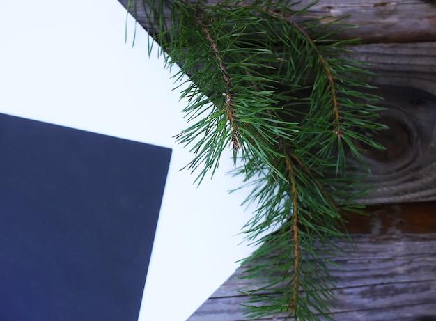 오래된 나무 배경에 빈 종이 시트가 있는 가을 오크 잎과 소나무 가지 구성