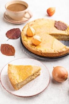 잎과 회색 콘크리트에 커피 한잔으로 장식 된 가을 양파 파이