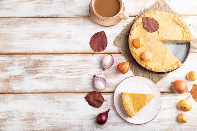 白い木製の葉とコーヒーのカップで飾られた秋のタマネギのパイ