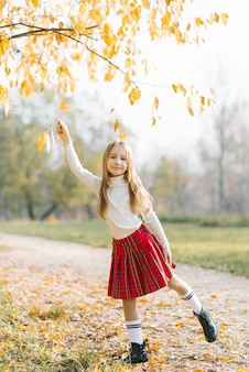 公園や森の中を歩いている美しい幸せな女の赤ちゃんの秋のオープンポートレート。
