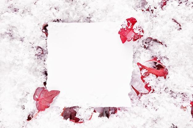 紙のモックアップで秋または冬のフレーム構成。赤い葉と雪の背景。最小限