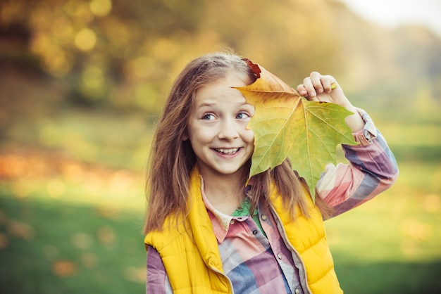 Autumn outdoor portrait of beautiful happy child girl walking in park or forest adorable happy girl ...