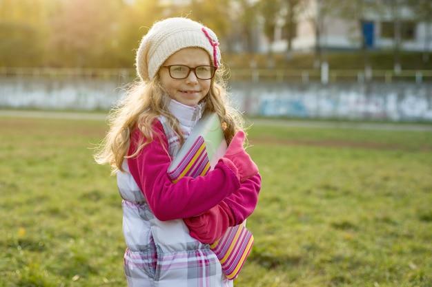 Autumn outdoor portrait of little schoolgirl.