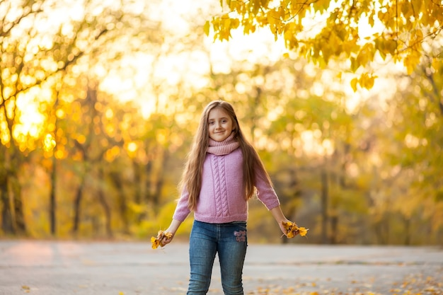 暖かいニットスカーフで公園や森を歩く美しい幸せな子の女の子の秋の屋外の肖像画