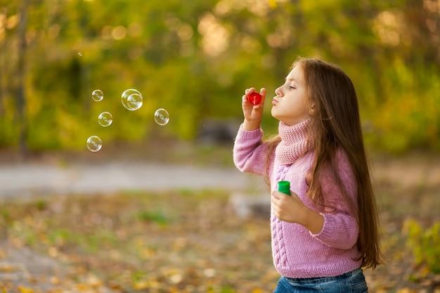 美しい幸せな子の女の子の秋の屋外の肖像画