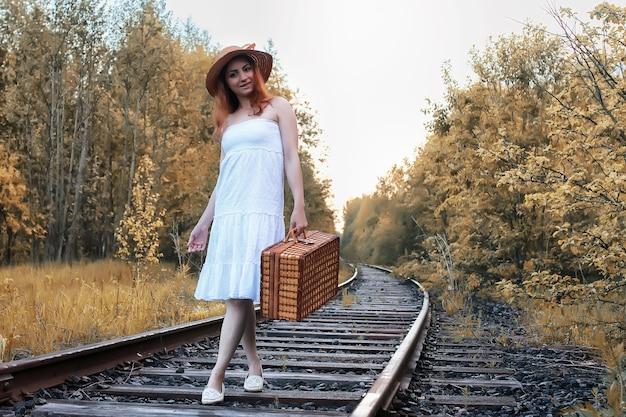 흰색 sundress와 레일 위를 걷는 고리 버들 가방에 가을 공원 소녀