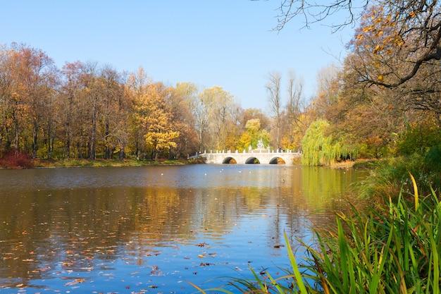 Осенний парк с деревьями над водами голубого озера, лазенки, варшава, польша