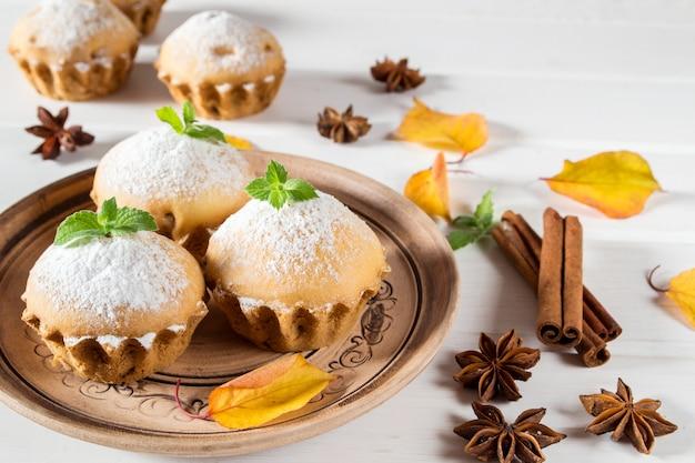 秋のペストリー。シナモンスティック、アニススター、秋の紅葉と粉砂糖を使った自家製カップケーキ