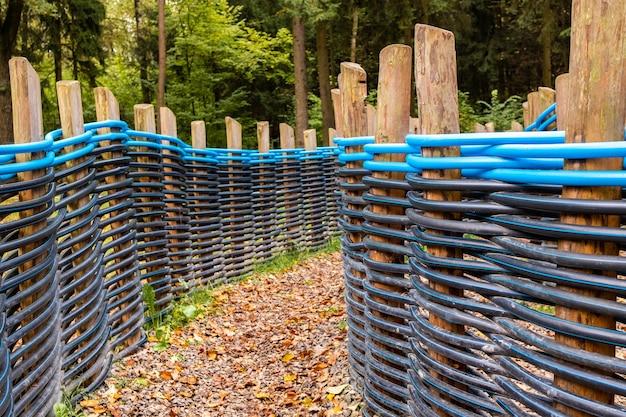 黒と青のねじれたプラスチックパイプで作られた柵の間に落ち葉が木の柱の間に編まれた秋の小道。ランドスケープデザインにおけるポリプロピレン配管パイプの代替使用。