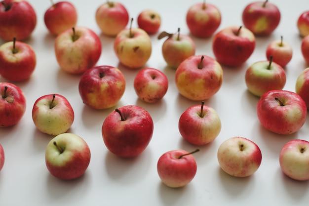 Осенний узор со свежими красными яблоками на белом фоне, вид сверху