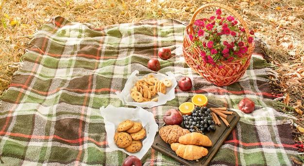 秋のピクニック。毛布の上に花が付いているバスケット。お茶、クロワッサン、クッキー、黄色い紅葉のブドウ。秋のコンセプト。バナー。スペースをコピーします。