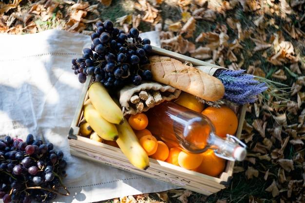 Осенний пикник в деревянном ящике с фруктами-виноградом, бананами, апельсинами и бутылкой питьевой воды.