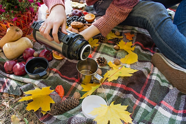 Autumn picnic in the park. girl pours tea from a thermos into a cup.