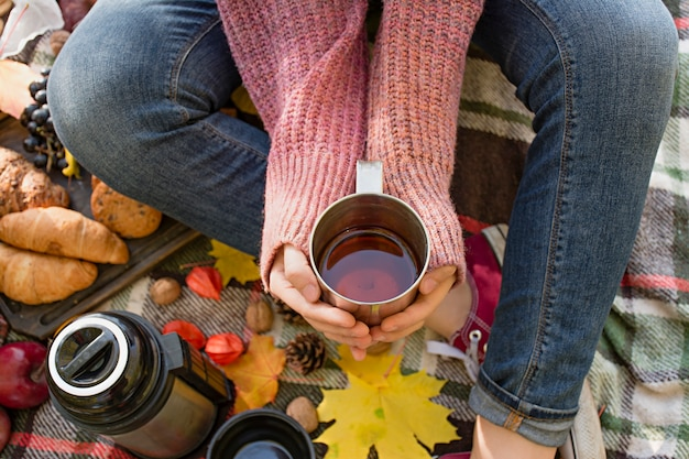 Autumn picnic in the park, warm autumn day. the girl holds a cup with tea in her hands. basket with flowers on a blanket in yellow autumn leaves. autumn concept.