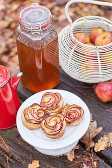 秋のピクニックテーブルのアイデアローズアップルマフィンの森、瓶にリンゴジュース、アンティークの赤いコーヒーメーカー