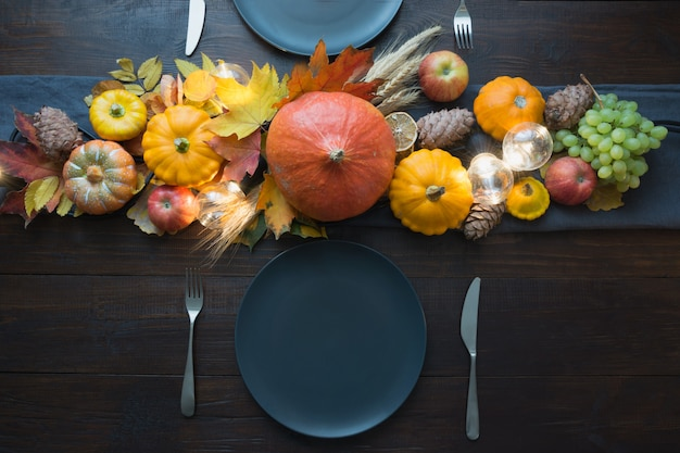 Autumn place setting with leaves, garland and pumpkins