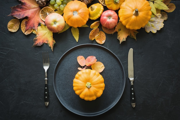 Autumn place setting with leaves and pumpkins