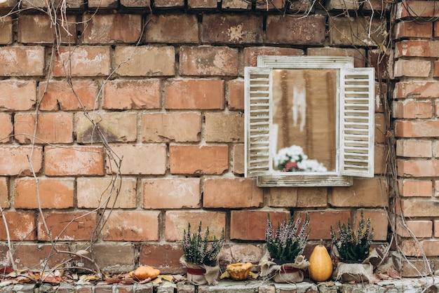 가을 베란다 장식. 벽돌 외관 배경에 식물이 있는 단풍, 호박, 냄비의 화환. 수확 개념