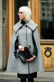 Autumn portrait of beautiful blonde woman in grey coat with black bag