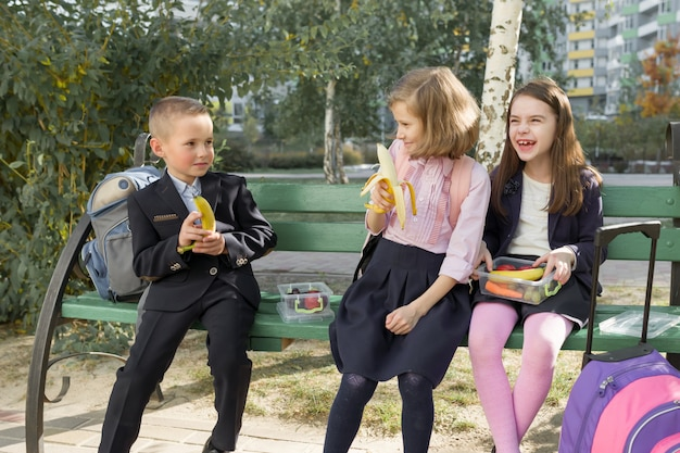 Autumn portrait of children with lunch boxes, school backpacks.