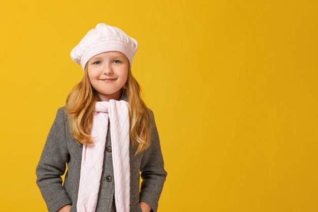 Autumn portrait of a little girl in a gray coat and beret.