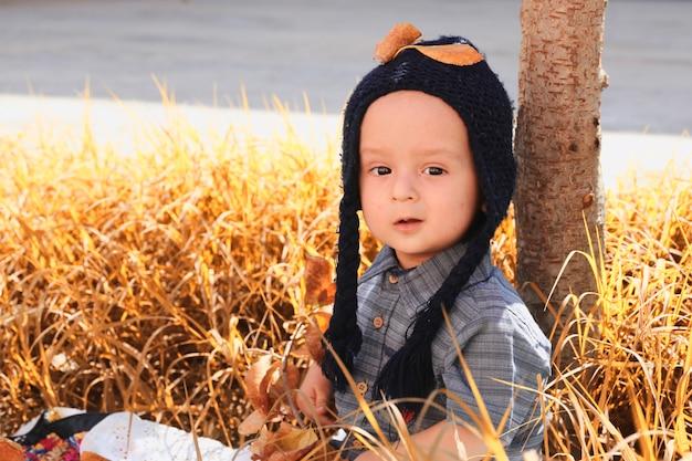 庭で2〜3歳の子供の秋の肖像画。秋のシーズン。ニットキャップの陽気な甘い混血男の子のクローズアップビュー