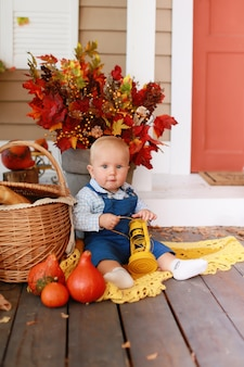 美しいヨーロッパの少年の秋の肖像画。秋の日に自宅の木製ポーチに座っている小さな金髪の少年。カントリーハウスの子供。赤ちゃんは幸せです。収穫