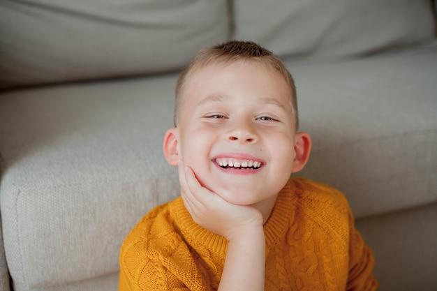 Осенний портрет маленького симпатичного мальчика в оранжевом свитере. уютный портрет мальчика, сидящего дома. падать.