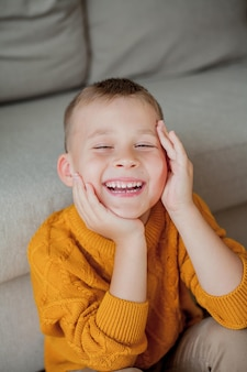 オレンジ色のセーターを着た小さなかわいい男の子の秋の肖像画。家に座っている男の子の居心地の良い肖像画。秋。