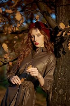 Осенний портрет женщины в шляпе, берете и плаще возле дерева в осенней желтой листве