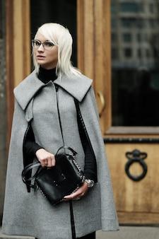 黒のバッグと灰色のコートで美しい金髪の女性の秋の肖像画