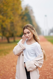 エレガントなコートで美しい若い女性の秋の肖像画