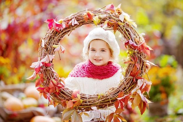 かわいい女の子の秋の肖像画。赤いブドウのかわいい女の子は、秋の公園で花輪を残します。