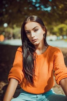 Осенний портрет модной молодой женщины, глядя на камеру