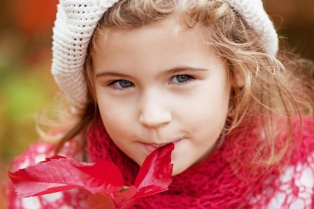어린 소녀의가 초상화입니다. 붉은 포도와 예쁜 소녀가 공원에 나뭇잎. 어린이를 위한 가을 활동. 가족을 위한 할로윈과 추수 감사절 시간.